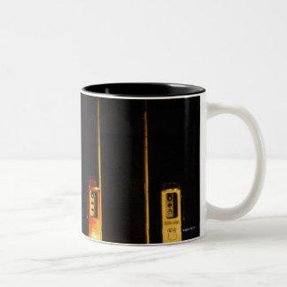 Surtidores de gasolina del vintage en la noche, cr tazas de café