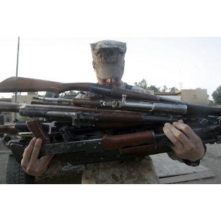 A marine readies 80 pounds of enemy rifles seiz