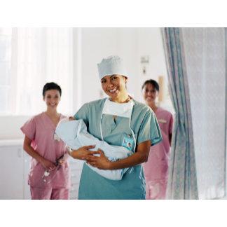 Delivery room nurse holding baby, nurses in