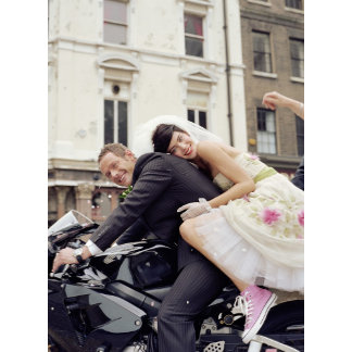 Bride and groom on motorbike, smiling, portrait