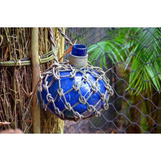 blue glass bottle in net against fence