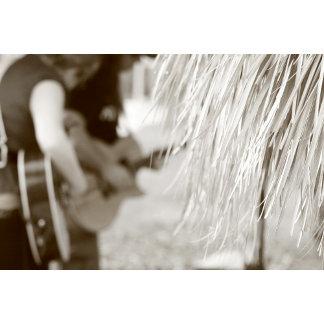 Guitar players behind tiki hut sepia toned