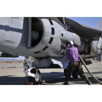 Aviation fuel technician attaches a fuel line