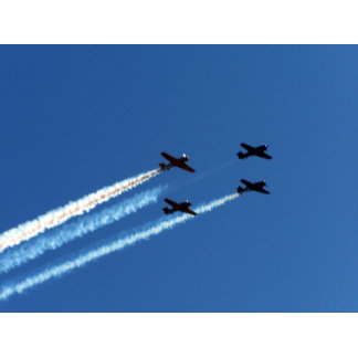 four flying planes with trails blue sky