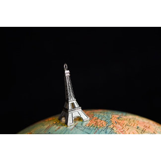 A statue of the Eiffel Tower on top of a globe