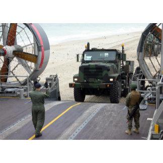 A loadmaster guides a Marine 7-ton truck
