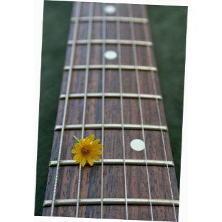 Yellow flower against guitar fingerboard