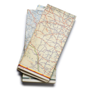 A stack of folded road maps on a white