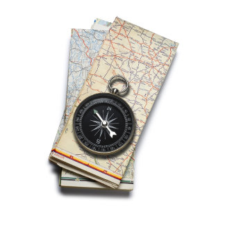 A compass sitting on a stack of folded road maps