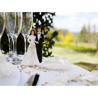 Bride and groom figurine on table by champagne