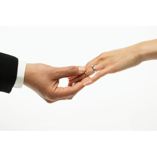 Man placing wedding band on woman's hand (focus