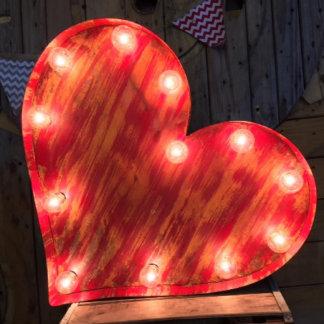 Muestra encendida corazón rojo rústico de la carpa