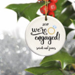 """Ceramic Couple's We're Engaged Christmas Ornaments<br><div class=""""desc"""">Smiling will come easy for couples as they gaze at the personalized gift ornament reflecting their names among the glitter and lights.  Produced with high quality ceramics,  the attractive round ornament will make a deluxe holiday housewarming or anniversary gift for your favorite newlyweds.</div>"""