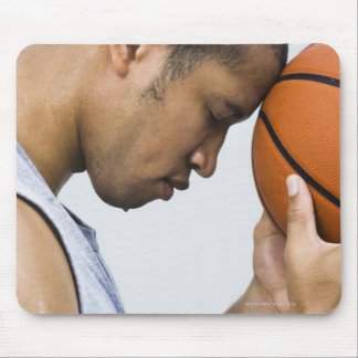 sweating man leaning forehead on basketball mouse pad