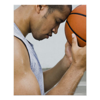 sweating man leaning forehead on basketball poster