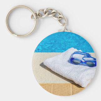 Swimming goggles and towel near swimming pool keychain