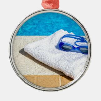 Swimming goggles and towel near swimming pool metal ornament