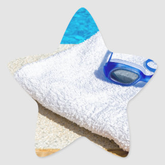 Swimming goggles and towel near swimming pool star sticker