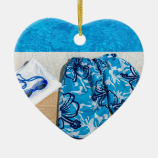 Swimming trunks goggles and towel at pool ceramic ornament