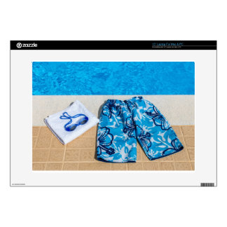 Swimming trunks goggles and towel at pool laptop skins