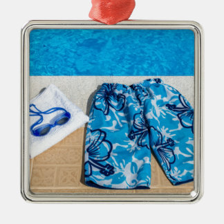 Swimming trunks goggles and towel at pool metal ornament