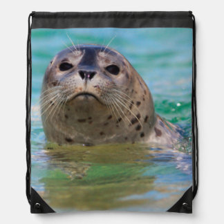 Swimming with a baby seal drawstring bag
