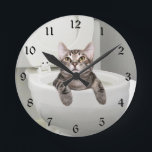 """Tabby cat in toilet round clock<br><div class=""""desc"""">Silver,  or gray,  tabby cat has been relaxing in his own personal swimming pool the bathroom commode or toilet and looks out so innocently.  Great for bathroom decor or just plain cat lovers.</div>"""