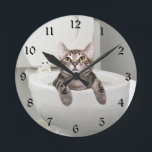 "Tabby cat in toilet round clock<br><div class=""desc"">Silver,  or gray,  tabby cat has been relaxing in his own personal swimming pool the bathroom commode or toilet and looks out so innocently.  Great for bathroom decor or just plain cat lovers.</div>"