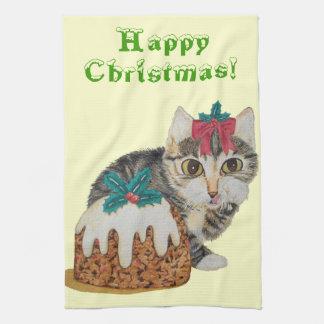tabby gris del gatito lindo que lame navidad de la toalla de cocina