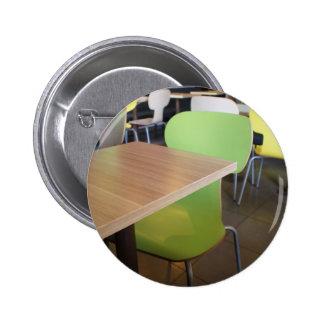 Tablas y sillas vacías en cafés pin redondo de 2 pulgadas
