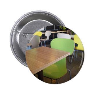 Tablas y sillas vacías en cafés sin los visitantes pin redondo de 2 pulgadas