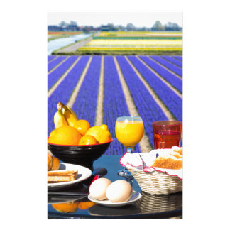 Table with food and drink near flowers field stationery