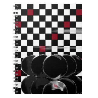 tablero de ajedrez negro del rojo del negro de los libros de apuntes con espiral
