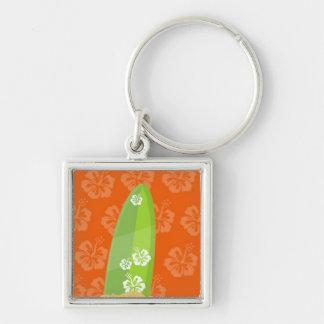 Tablero de resaca verde en el fondo anaranjado de  llavero cuadrado plateado