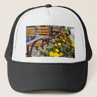 Tables and chairs with flowers trucker hat