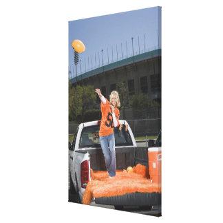 Tailgating woman throwing football canvas print