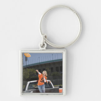 Tailgating woman throwing football keychain