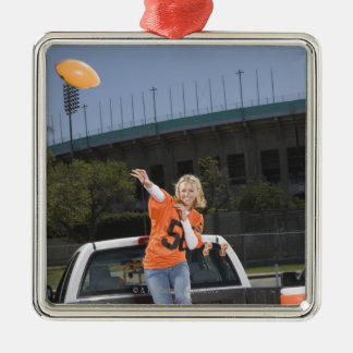 Tailgating woman throwing football ornament