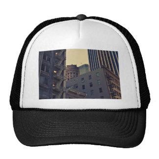 Tall buildings crowd the sky in the city trucker hat
