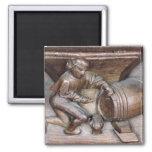 Talla representando a un hombre que pone un golpec imán cuadrado