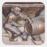 Talla representando a un hombre que pone un pegatina cuadrada