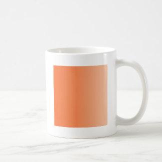 Tangelo a la pendiente de la vertical del albarico taza de café