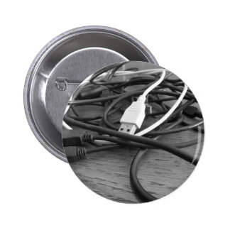 Tangle of dusty computer cables with sockets pinback button