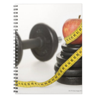 Tape measure, apple, dumbbell and weights notebook