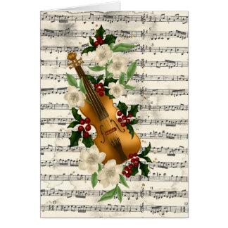 Tarjeta de Navidad del violín en la hoja de música