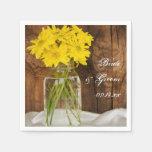 Tarro de albañil y margaritas amarillas que casan  servilleta de papel