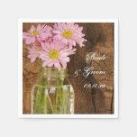 Tarro de albañil y margaritas rosadas que casan servilleta de papel