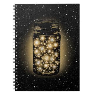 Tarro que brilla intensamente de luciérnagas con l note book