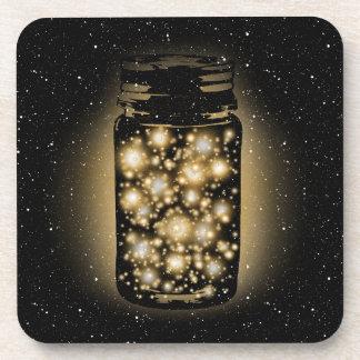 Tarro que brilla intensamente de luciérnagas con l posavaso