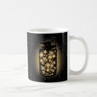 Tarro que brilla intensamente de luciérnagas con taza de café